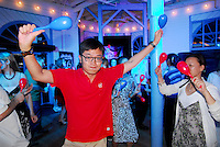 Chinese journalists dances at the Santa Monica Pier Carousel during the Shanghai GM/Cadillac Route 66 Celebration on Friday, August 17, 2012.