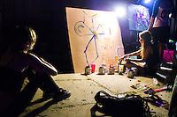 A woman paints an art piece as festival goers watch nearby.