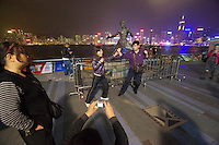 Kowloon, Avenue of the Stars, a seaside promenade along Hong Kong Harbour. People taking souvenir photos in front of the skyline and with the Bruce Lee statue.