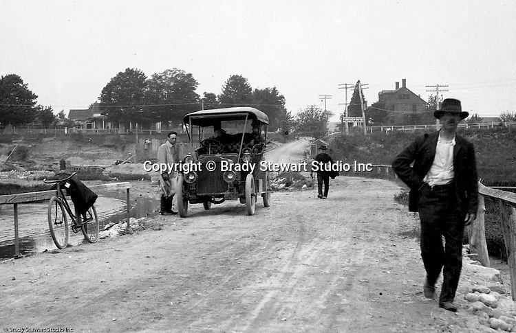 Westmoreland County PA:  Brady Stewart and friends stopped along the road to pose for a photograph in the new 1906 Buick Model F.  Two men walking home from town and the Fair View Hotel is in the background (over shoulder of man walking)