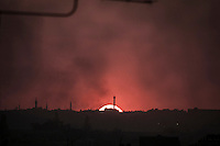The sun sets up at the sunset as smoke rises over the old city district where the heavy fighting and shelling have taken place during the battle in the last week between rebel forces and Syrian army for the control of Aleppo City.