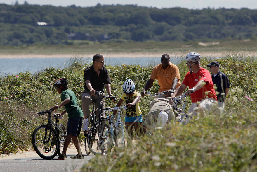 U.S. President Barack Obama rides bikes with family and friends along Lobsterville Beach in Aquinnah on Martha's Vineyard.   On the right in the yellow shirt is his daughter Sasha....
