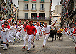 A runner falls in front of El Pilar bulls during the fourth run of the bulls of the San Fermin festival, on July 10, 2012, in the Northern Spanish city of Pamplona. The festival is a symbol of Spanish culture that attracts thousands of tourists to watch the bull runs despite heavy condemnation from animal rights groups . (c) Pedro ARMESTRE