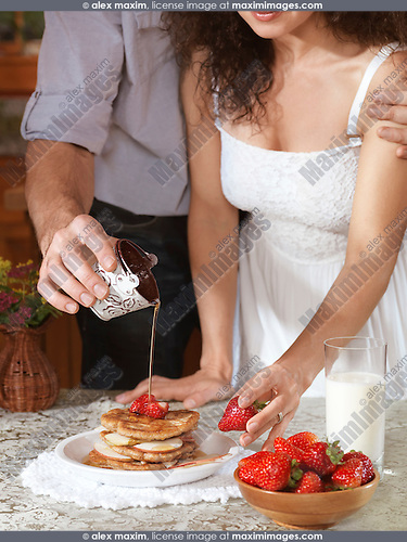 Young couple making a plate of pancakes with strawberries an apples together in the kitchen