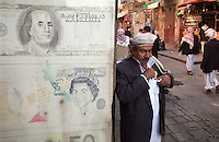 Currency shop in Sana'a, an ancient centre for international trade, advertised with reproductions of US dollar and British pound notes.