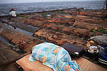 MBANDAKA, DEMOCRATIC REPUBLIC OF CONGO JUNE 29: An unidentified man sleeps on a straw mat while travel on a boat made of big trees on the Congo River on June 29, 2006 outside Mbandaka, Congo, DRC. The boat traveled with about 150 passengers from Bumba to Kinshasa, a journey of about 1300 kilometers. The Congo River is a lifeline for millions of people, who depend on it for transport and trade. Passengers slept in the open, with their goats, pigs and other animals. Boat travel is the only option for most people along the river as there?s no roads or infrastructure. Very few can afford to fly in a plane to the capital Kinshasa. During the Mobuto era, big boats run by the state company ONATRA dominated the river. These boats had cabins and restaurants etc. All the boats are now private and are mainly barges that transport goods. The crews sell tickets to passengers who travel in very bad conditions. The conditions on the boats often resemble conditions in a refugee camp. Congo is planning to hold general elections by July 2006, the first democratic elections in forty years. The Congolese and the international community are hoping that Congo will finally have piece and the country will be rebuilt..(Photo by Per-Anders Pettersson/Getty Images)..
