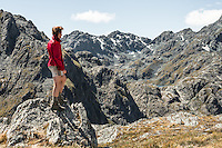 Hiker on Conical Hill 1515m on Routeburn Track looking towards Lake Wilson visible centre right, Mt. Aspiring National Park, UNESCO World Heritage Area, Central Otago, South Island, New Zealand, NZ
