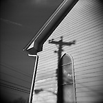 Monochrome Holga image of a church facade and window with cross-like shadow of telephone pole