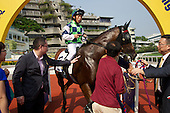 An unidentified winning jockey with horse owners at the Hong Kong Jockey Club's Shatin Racecourse.