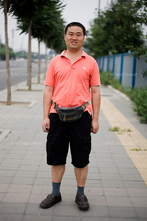 Boweijun, an engineer, age 36, poses for a portrait in Beijing. Response to 'What does China mean to you?': 'China is just the name of a country.'  Response to 'What is your role in China's future?': 'A builder. Occasionally the people bring up suggestions, but nobody listens.'