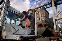 A driver washes his windshield while waiting to unload a container ship at the Port of Oakland, the 4th largest port. Officials says that they have been working toward having cargo ships exchange their ballast water at sea before entering San Francisco Bay. The fouling of water with invasives happened historically when the oyster industry was running in CA. But in recent history, cargo ships and tankers have been blamed.<br /> Cargo ships carry less water and dump less water, and they are starting to exchange at sea more often. But the <br /> numbers of cargo ships is on the increase. No one knows the effect of increased numbers but less water fouling--organisms that live in ocean waters are not going to survive the bay waters in high numbers. Oil tankers carry more water, but they carry it longer (lesser <br /> survival rate of organisms)--also the Alaskan Valdez port is likely most vulnerable to tankers because they dump when exchanging for a heavy load of oil before heading south.