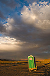 Green fiberglass portable outhouse and a trailer along US 95 in cental Nevada