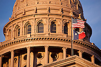 Close-up of the State Capitol Dome in Austin, Texas with US and Republic of Texas Flags waving in the wind amid a vibrant blue sky.
