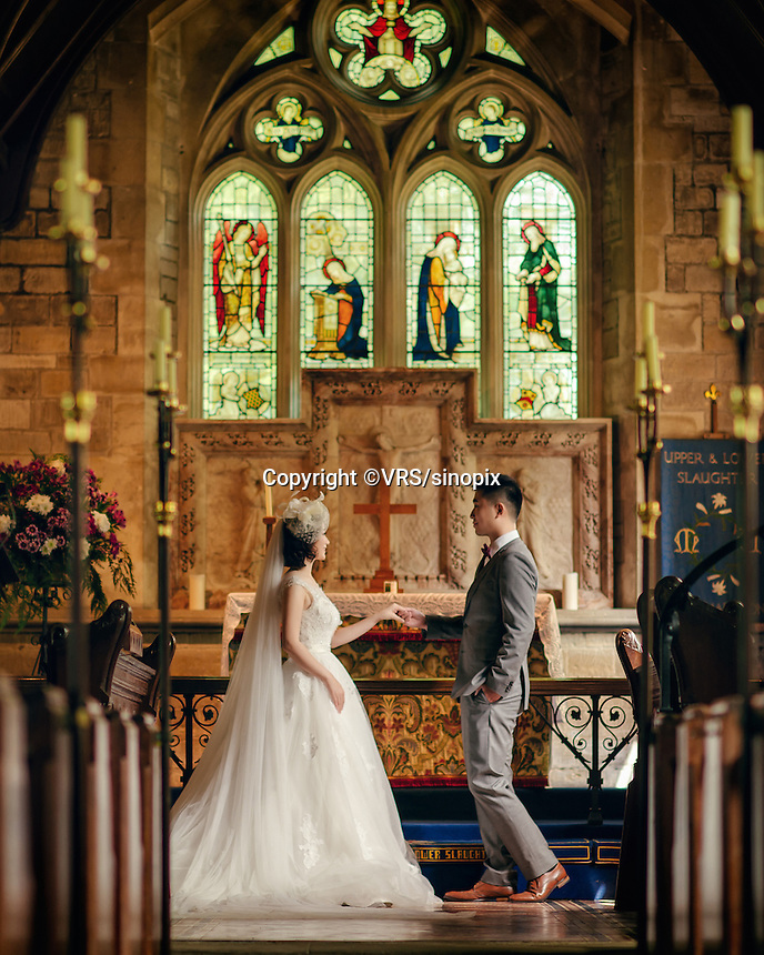 A Chinese couple pose for their wedding photos in St Mary's Church, Lower Slaughter, The Cotswolds, UK.  Chinese couples often use the church for wedding photos. An increasing number of Chinese couple are having their wedding photos taken in the English country-side, classic towns and monuments to show in China. <br /> <br /> Photo by Sinopix