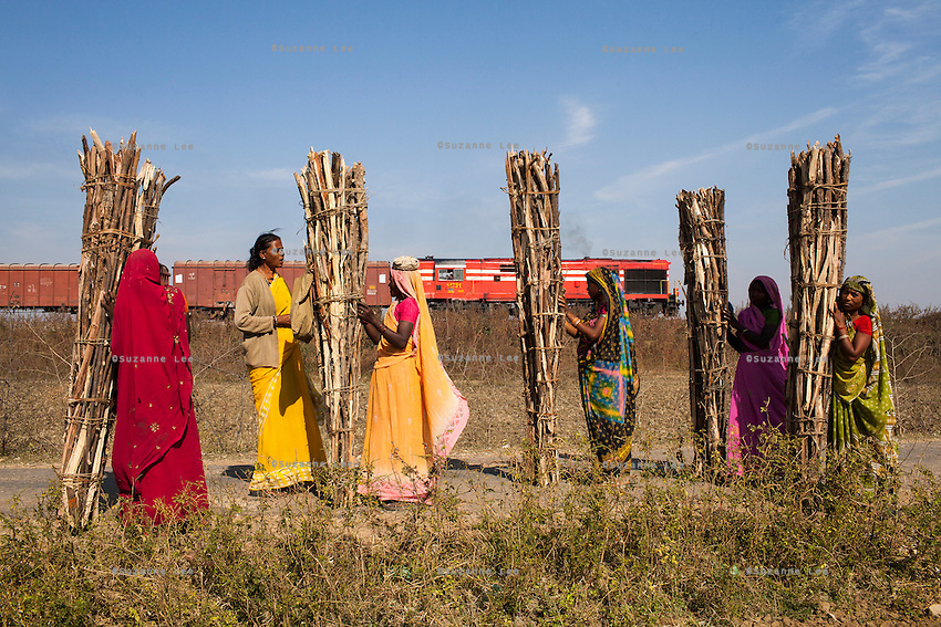 Shanti Adivasi (in yellow saree), 52, interviews a group of tribal women, as they take a break from their work carrying gathered firewood from the jungles to be sold in the towns, in Manikpur, Chitrakoot, Uttar Pradesh, India on 6th December 2012. Shanti used to be a wood gatherer, working with her parents since she was 3, and later carrying up to 100 kg of wood walking 12km from the dry jungle hills to her home to repack the wood which sold for 3 rupees per kg. After learning to read and write in an 8 month welfare course, at age 32, she became a reporter, joining Khabar Lahariya newspaper since its establishment in 2002, and making about 9000 rupees per month, supporting her family of 14 as the sole breadwinner. Photo by Suzanne Lee for Marie Claire France.