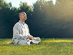 Shaolin monk meditating outdoors in the nature during sunrise sitting on grass in sunlight