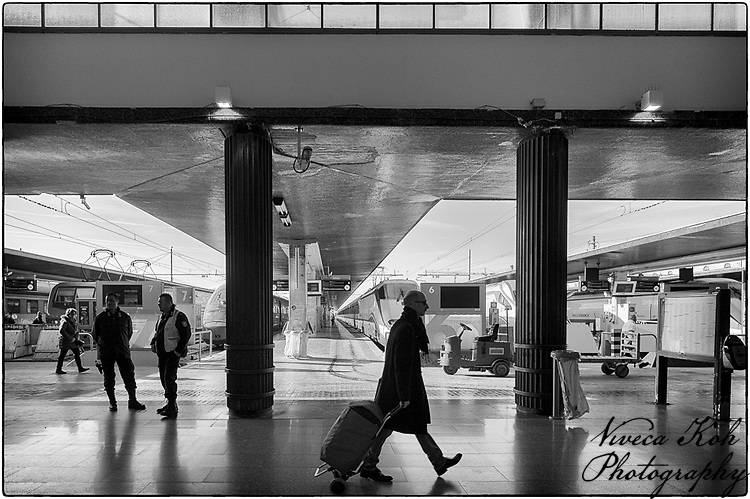 Man pulling suitcase walking along concourse of Ferrovia station, Venice, Italy, with trains in background.