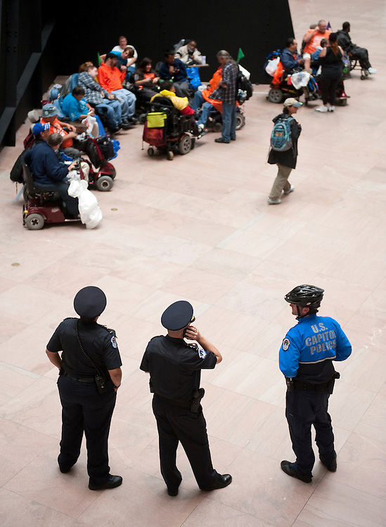 "UNITED STATES - SEPTEMBER 20: U.S. Capitol Police keep watch as dozens of ADAPT protesters, most of them in wheelchairs, gather for a silent protest in the atrium of the Hart Senate Office Building on Tuesday, Sept. 20, 2011. The group of disability rights activists were on Capitol Hill to call on ""Super Committee"" Republicans to ensure that Medicaid dollars are invested in community based health care programs. A press release from the group says 54 ADAPT activists were arrested at the offices of Reps. Hensarling and Camp yesterday. (Photo By Bill Clark/Roll Call)"