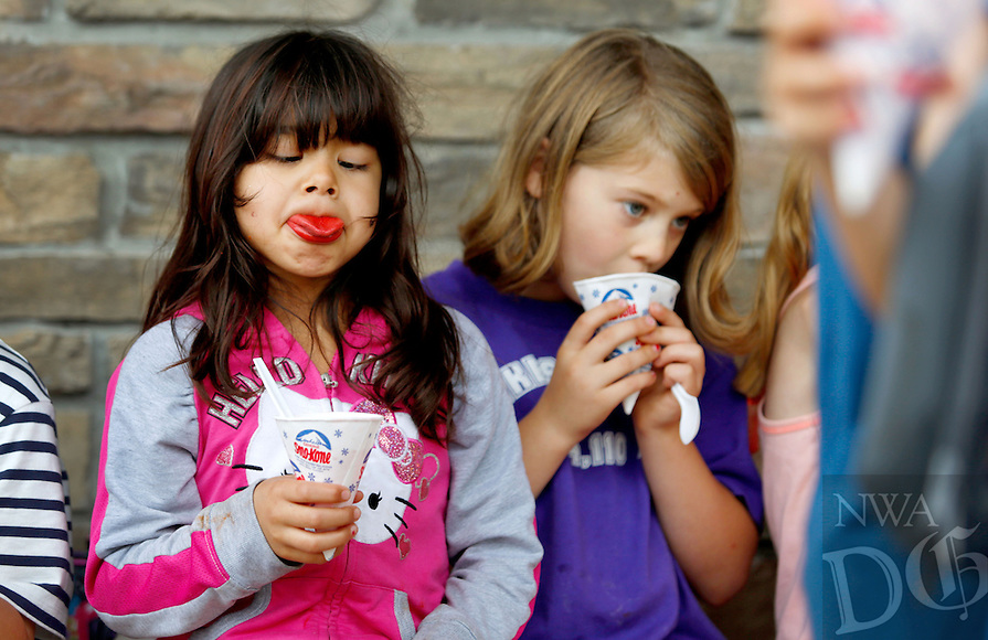 NWA Media/JASON IVESTER --06/05/2014--<br /> Zuri Aguilar (left) tries to see the color of her tongue while having a snow cone with Ella Estes, both Cooper Elementary first-graders, on Thursday, June 5, 2014, outside the Bella Vista school. Representatives from Arvest Bank came to the school and made snow cones for all the students as a celebration for their last day of the school year.
