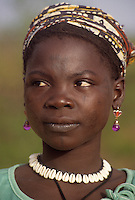 Near Niamey, Niger. Young  Fulani Woman wearing Cowrie Necklace, Earrings, and Headscarf.  Light Facial Scarffication, a form of tribal identification, can be seen on her forehead, her cheeks, and on either side of her mouth.  Cowries are often used as jewelry in Niger, though the country may be eight hundred miles from the sea.