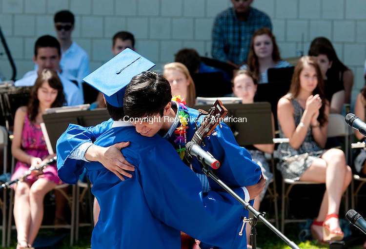 WOODBURY, CT-062114JS08--Nonnewaug High School Jonas Berry and Ian Pedorza hug one another after singing &quot;Live Like We're Dying&quot; during graduation ceremonies Saturday at the school in Woodbury.<br /> Jim Shannon Republican-American