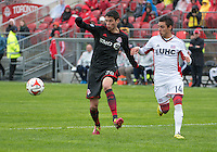 Toronto, Ontario - May 3, 2014: New England Revolution forward Diego Fagundez #14 and Toronto FC defender Mark Bloom #28 in action during a game between the New England Revolution and Toronto FC at BMO Field.<br /> The New England Revolution won 2-1.