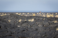 An age group triathlete rides through the lava fields on the bike at the 2013 Ironman World Championship in Kailua-Kona, Hawaii on October 12, 2013.