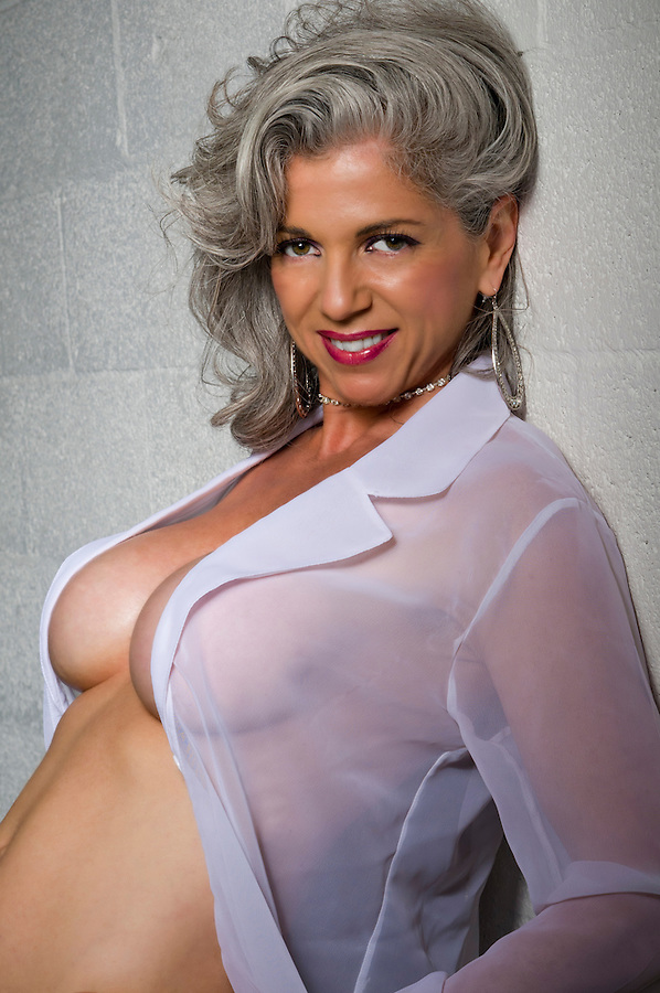 Very attractive woman at her fifties posing with transparent shirt.