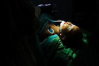 A young child lying in an operating theatre after surgery to repair a cleft in his soft palate, Bali, Indonesia.