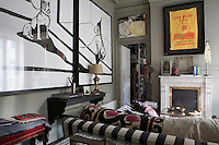 Gaspar Sobrino's signature bulldog, is immortalized in a diptych on the wall of the living room of his Madrid apartment. The room features a classic white marble fireplace and a deep sofa strewn with antique Indian textiles in black, white and fuschia