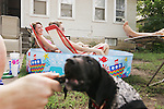 CHAD PILSTER &bull;&nbsp;Hays Daily News<br /> <br /> (left to right) Fort Hays State University students Dakota Thomas, from Garden City, plays with his dog Ranger, a 10 week labrador and pointer, while Ashley Bowles and her sister Lacey Bowles, from Lindsborg, lounge in the pool as A.J. Brown, from Topeka, reads a book on  Monday, June 17, 2013, along West 6th St. in Hays, Kansas. Brown, said a friend and himself bought the pool on a whim one day when they were in WalMart and thought &quot;We need a pool.&quot;