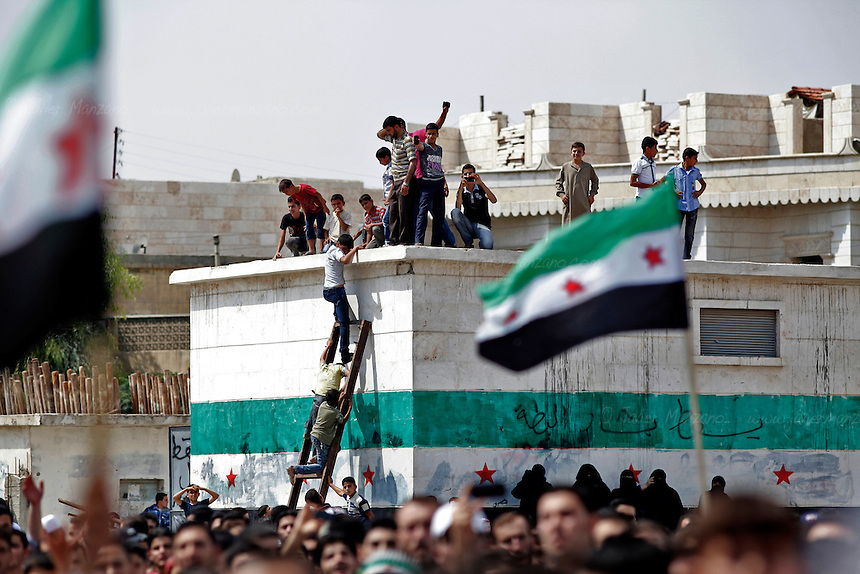 Residents from the northern Syrian town of Al Bab organized a peaceful protest at a main square renamed after the revolution began as &quot;Freedom Square&quot;. More than a thousand people gathered to sing and chant anti-Assad slogans - minutes later, the square emptied as the sound of a fighter jet from the Assad air force began to circle the square. As the people scattered, a blast was heard followed by three other explosions. The fighter jet made at least 6 passes as it fired its 50 caliber  machine gun on the neighborhood below. Doctors at the local underground hospital did not allow this reporter access to the facility because of the load of patients coming in. Unconfirmed reports by the FSA spokesperson in Kilis say that 7 people died and 50 were injured. <br />