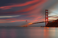 Fog over the Golden Gate Bridge at sunset, San Francisco, California, USA.