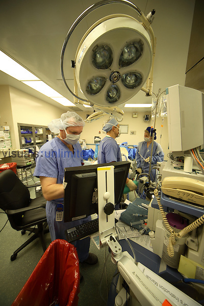 An anesthesiologist entering data into the anesthesia computer. A CRNA  is seen in the middle of the photo, and a circulating nurse is on the right.