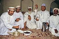 Nizwa, Oman, Arabian Peninsula, Middle East - Omani Men Having Dates and Coffee at Nizwa Fort.  Four are wearing the Omani turban, called msarr, or massar.  The fifth wears an embroidered Omani cap, called kumma.  All are in white dishdashas, the traditional Omani robe.