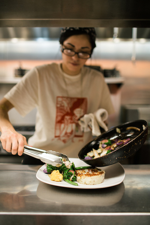 Raleigh, North Carolina - Thursday November 12, 2015 - Roxie Avila plates vegetables for the BBQ dish at Fiction Kitchen in Raleigh.