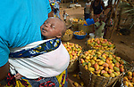 A sleeping baby ignores mangoes for sale in the market in Sonougouba, Mali, where the ACT Alliance has worked with local residents to encourage a sustainable economy, increase food security, and improve local governance.