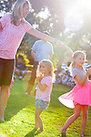 Kelli Granum of Los Altos, far left, twirls her daughter MacKenzie while sibling Chloe, center, dances to the music at a the Summer Concert Series performance June 13.
