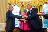 U.S. President Donald J. Trump (R) shakes hands with Attorney General Jeff Sessions (L) while Sessions' wife,  Mary Blackshear Sessions (C) looks on shortly after Sessions was sworn by Vice President Mike Pence in the Oval Office of the White House in Washington, DC, USA, 09 February 2017. On 08 February, after a contentious battle on party lines, the Senate voted to confirm Sessions as attorney general.<br /> Credit: Jim LoScalzo / Pool via CNP