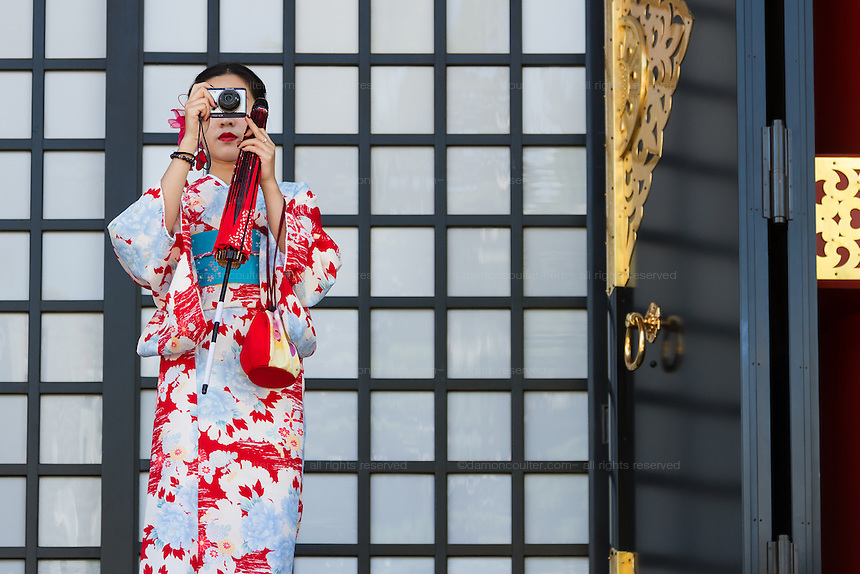 A woman in a kimono takes a photo at Senso-ji temple in Asakusa, Tokyo, Japan. Friday May 13th 2016