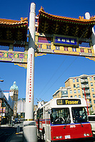 The number 8 Fraser bus passing through the Chinatown Gate into Chinatown, with Sun Tower in background, Vancouver, BC.