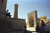 Sellers of carpets and tourist souvenirs sit in the shade outside the Kalan Mosque and Medressa, once an important Islamic studies teaching school in the Old Silk Road city of Bukhara. The minaret was built by Arslan Khan in  1127. Uzbekistan.