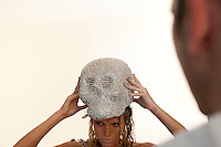 Jeweler-to-the-stars Rodrigo Otazu (R) watches as a model place a skull covered in Swarovski crystals on her head during a photo shoot, in New York, 8 November 2009.