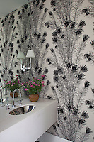 The walls of the cloakroom are upholstered in a monochrome fabric by Florence Broadhurst featuring a design of peacock feathers