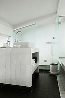 In this functional bathroom floor, walls and surfaces are covered in black or white ceramic tiles