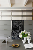 A useful blackboard has been built in to the kitchen cupboards; the work surface and sink are elegant grey Corian