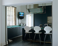 This contemporary kitchen has glass worktops, the central island doubling as an informal dining area
