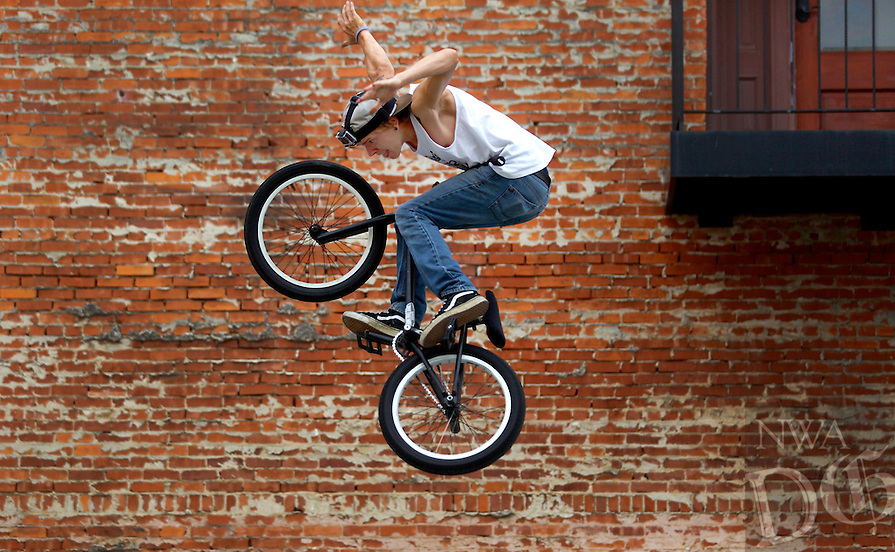 STAFF PHOTO JASON IVESTER --07/18/2014--<br /> Dylan Gunnell, 22, of Stuttgart jumps his bike on a temporary skate park setup on Friday, July 18, 2014, during Main Street Rogers' 3rd Friday in downtown Rogers. The theme for this month's event was &quot;Bike to the Bricks.&quot;