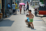 """Children play in the Manila North Cemetery. Hundreds of poor families live here, dwelling in and between the tombs and mausoleums of the city's wealthy. They are often discriminated against, and many of their children don't go to school because they're too hungry to study and they're often called """"vampires"""" by their classmates. With support from United Methodist Women, KKFI provides classroom education and meals to kids from the cemetery at a nearby United Methodist Church."""