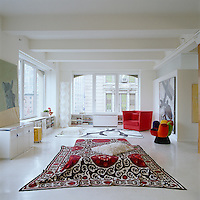 Large corner windows allow light to pour into the large living area which is scattered with rugs and colourful modern seating